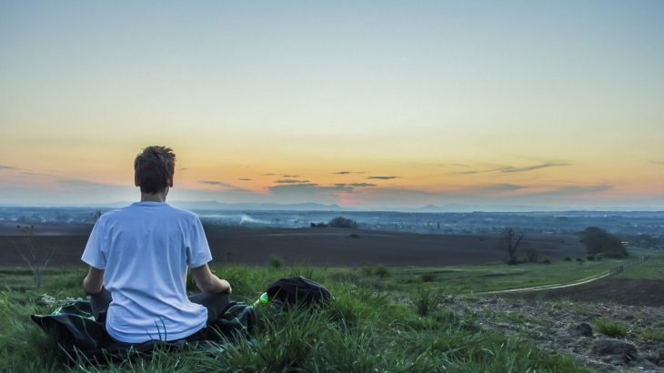 male-meditating-outside-the-city